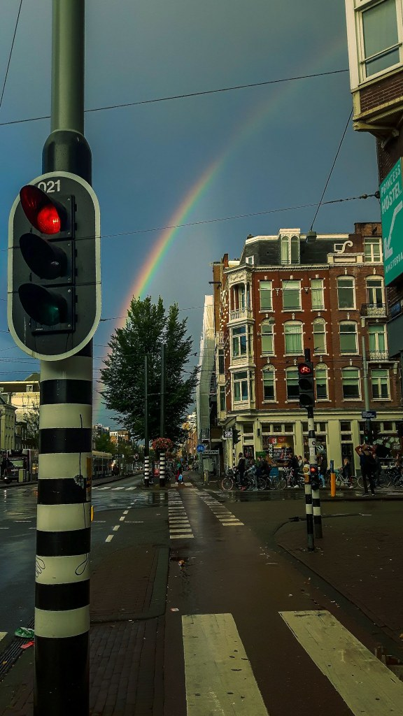 Street photography in Amsterdam on a traffic light while watching the rainbow