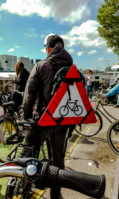 A guys with a bicycle sign on his backpack