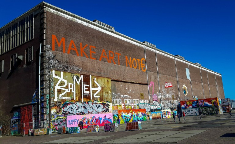 A former shipyard NDSM with graffiti: Make art not Euros
