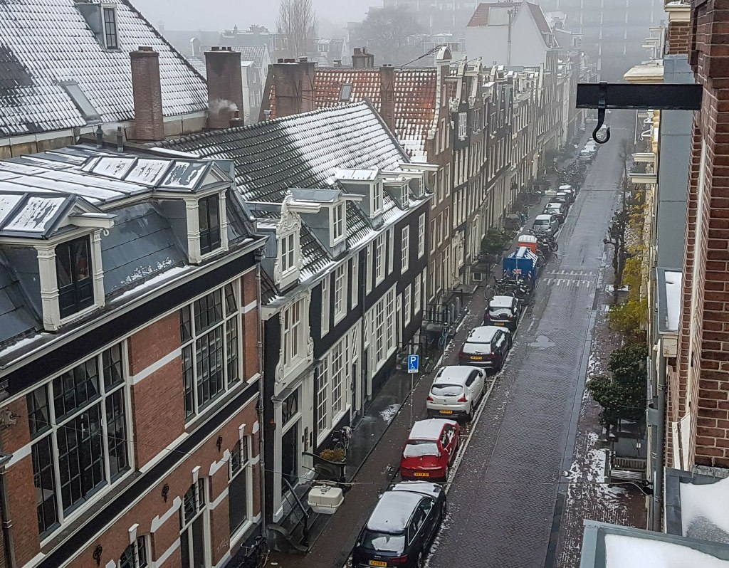 Snowy day in Amsterdam streets and roofs full of snow
