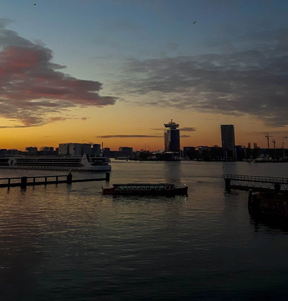 Sunset view and a boat on IJ river looking on Amsterdam North