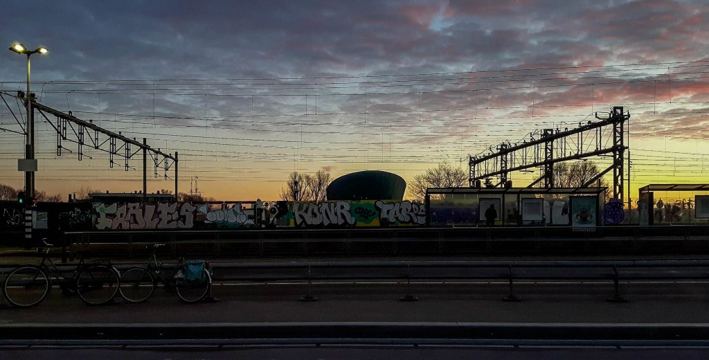 Urban art graffiti and NEMO museum in Amsterdam during the sunset