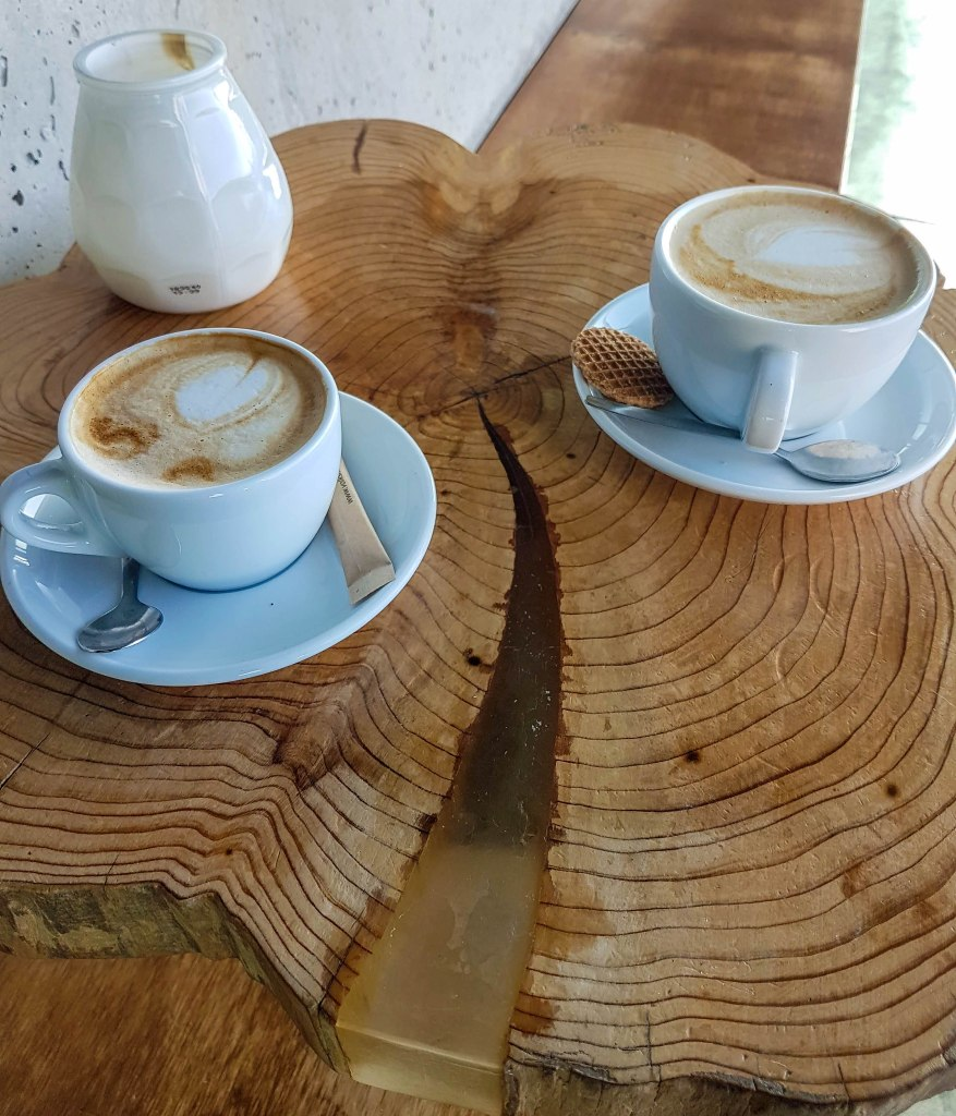 Two cappuccino coffees on a DIY table