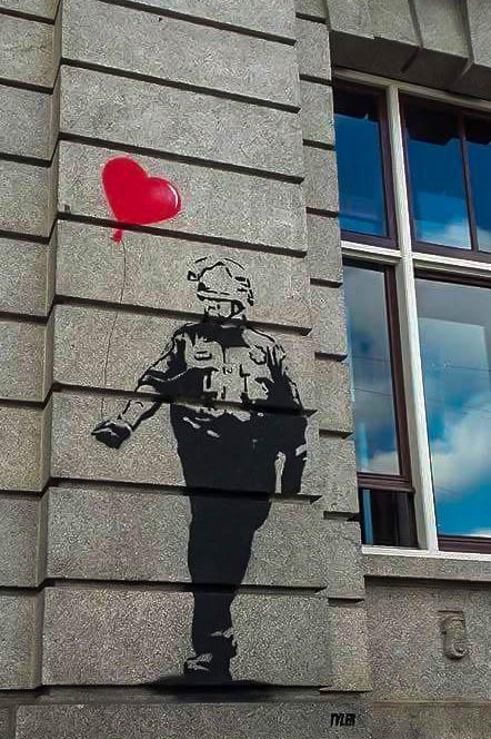 Tyler Street Art of a soldier holdin a heart baloon in Prins Hendrikkade in Amsterdam Dutch capital