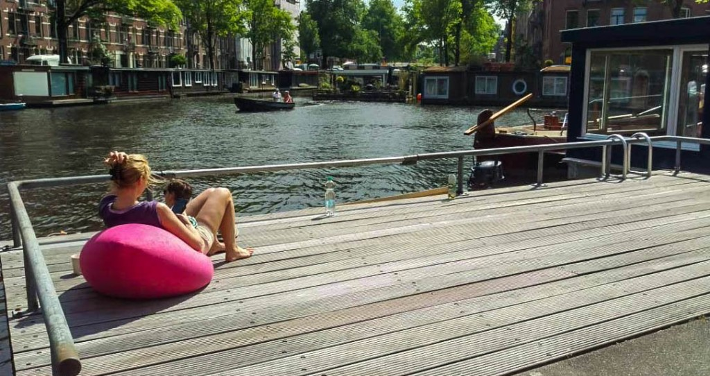 Woman sitting next to a Amsterdam canal and enjoying the sunny day