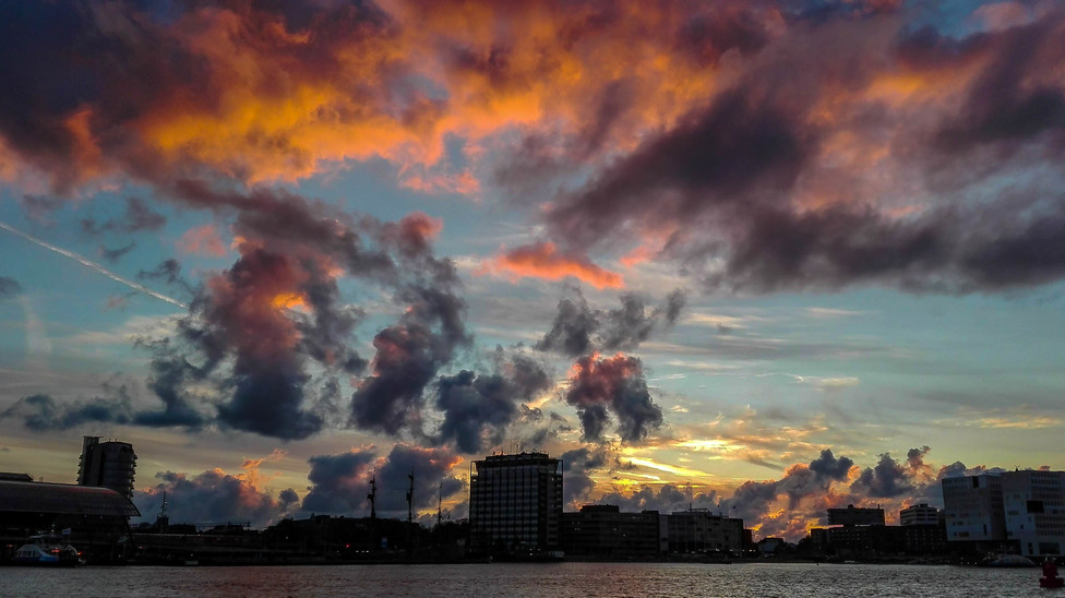 Colorful clouds during the sunset time captured from the Buiksloterweg ferry in Amsterdam city