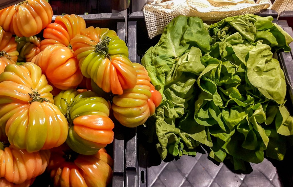 Fresh green salad and tomatoes on the shelves of Ekoplaza