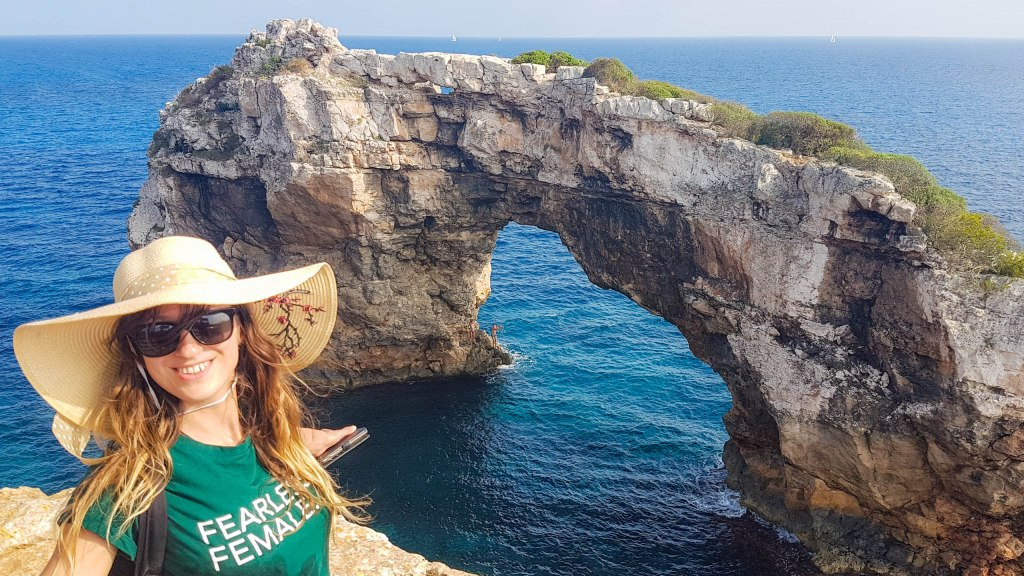 Me wearing a hat and fearless woman T-shirt next to Es Pontàs arch in Mallorca, Balearic islands, Spain