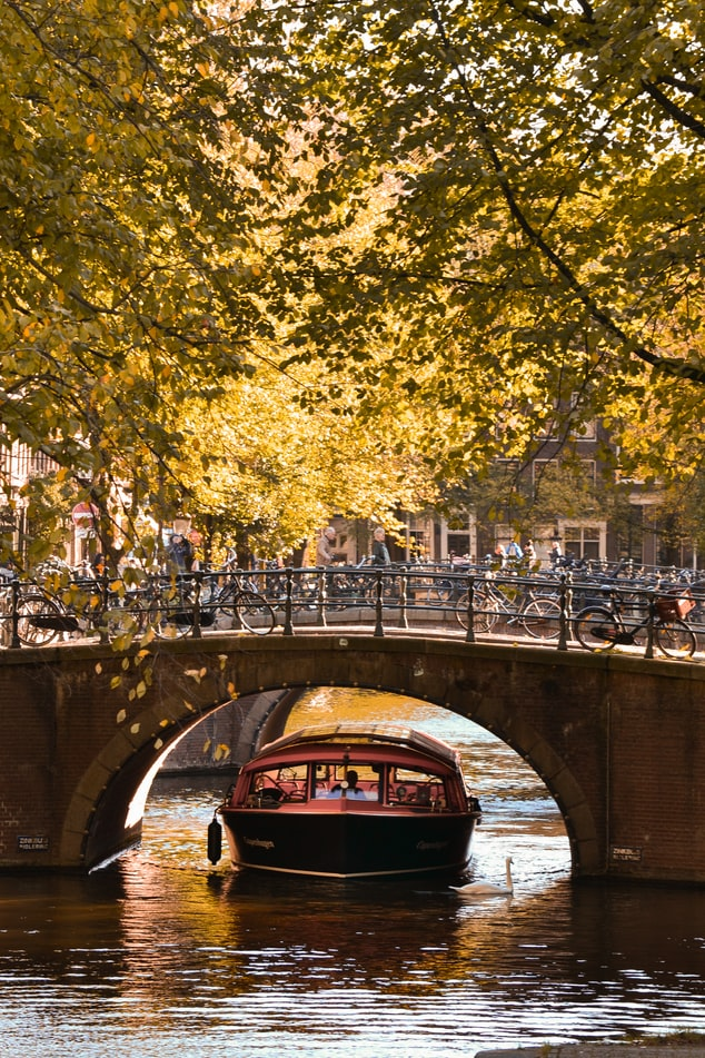 Boat under the bridge in Amsterdam canals