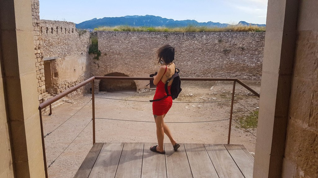 A girl in red inside of the Miravet castle on the top of the staircase