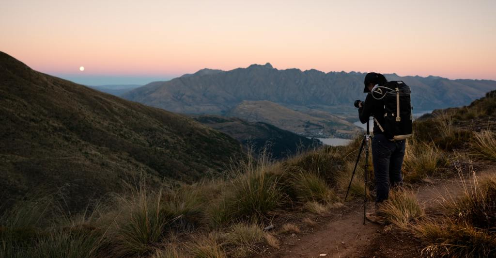A man filming the sunset using his camera and a tripod