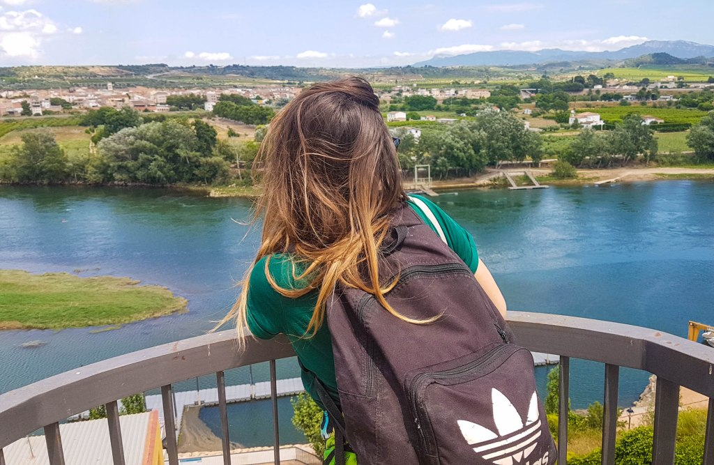 A girl with Adidas backpack looking over the river