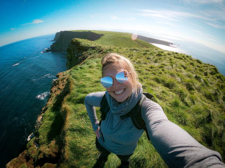 A girl with sunglasses on island cliff